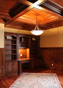 oak-paneled den with built-in oak cabinets and fireplace